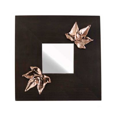 Mirror with two Ivy Leaves, made of shiny copper, placed on wooden mirror.
